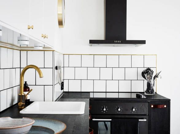 Black and white industrial kitchen with brass details by ApartmentStudios