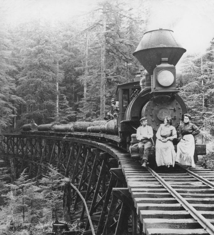 1906- People sit on the front of a logging train as it crosses a trestle bridge in the Cascade Mountains in Oregon. GETTY IMAGES