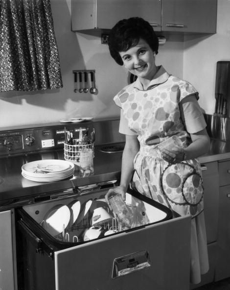 a housewife removes clean dishes from her automatic dishwasher | 1955 | #vintage #1950s #home #kitchen