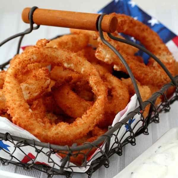 Recette traditionnelle américaine des célèbres onion rings, ces anneaux d'oignons frits accompagnés de leur sauce ranch ou d'une sauce barbecue.