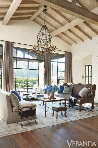 "While curtains protect from daytime glare, they serve a visual purpose as well: ""The roof pitch lines are not high, so I hung the drapery at the top of the wall to lift the eye."""