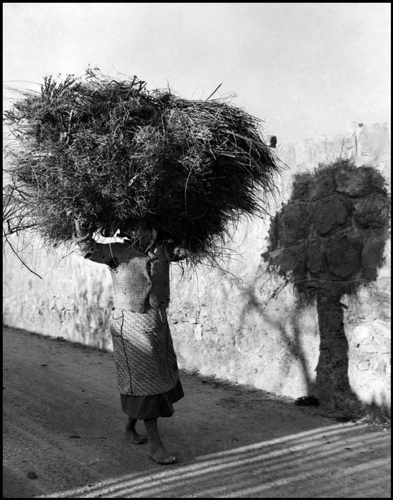 David Seymour, Woman carrying a large bundle on her head, Calabria, Italy, 1950.