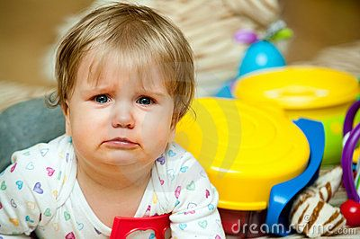 Portrait of crying baby girl with toys in background.