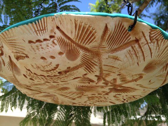 Casa rural playa comedero aves baño es hecho a mano en los Estados Unidos. La superficie superior es un hermoso esmalte Caribe que es asy e limpia y preciosa en el sol. La superficie inferior es realzada con un real conchas de California presiona en el clay.design mojado. También cuenta con un un glaseado ligero de rubbeid ocre oscuro quemado en la textura fabulosa. Sus pájaros les encantará. Incluido y conectado es una cadena de 12 pulgadas para colgar fácilmente. Cada uno es única hecha a…