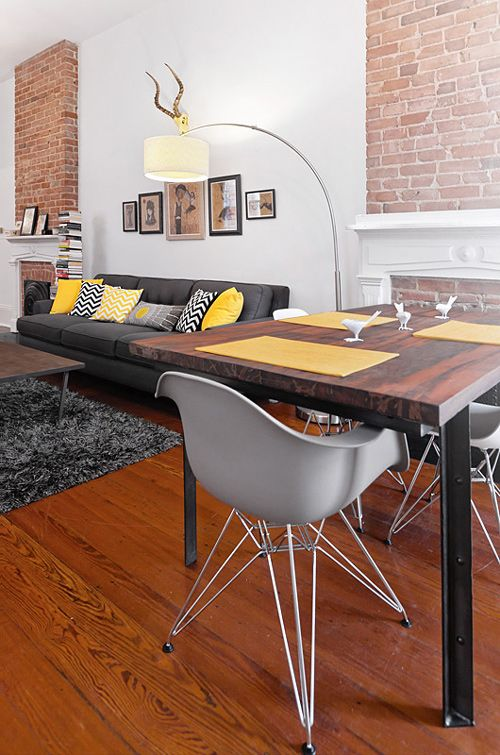 I love it all. Fantastic brick fireplaces, grey sofa with wonderful yellow color pops, West Elm railroad tie table with gorgeous wood top, Eames chairs...and so much more.