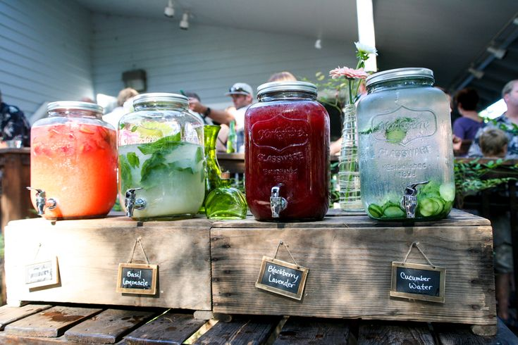Beverage station.  Two gallon mason jar drink dispensers.  Chalkboard signs.  Rustic vintage crates.  Table with shelf made from pallets.  All available to rent from #motifeventrentals.