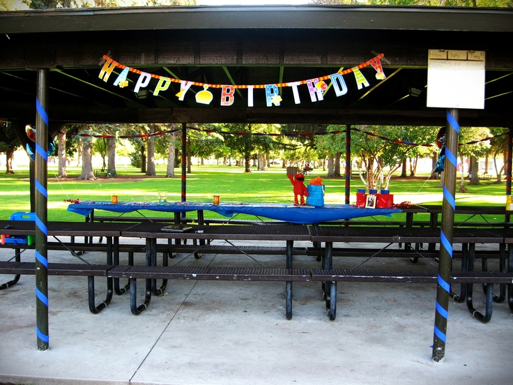 Outdoor party at a park pavilion, decorated using streamers, banner, and tablecloths in primary colors from the $store.
