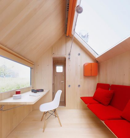 The dry living area is also split into two, corresponding to the gable as much as to the footprint of the house.A desk sits in front of a window positioned just above its surface. Below the skylight is a couch that doubles as a bed. These openings bring a lot of light into the small space, but blinds (orange, like many of the project's details) help to close off the space — to keep it from getting too hot, for example.