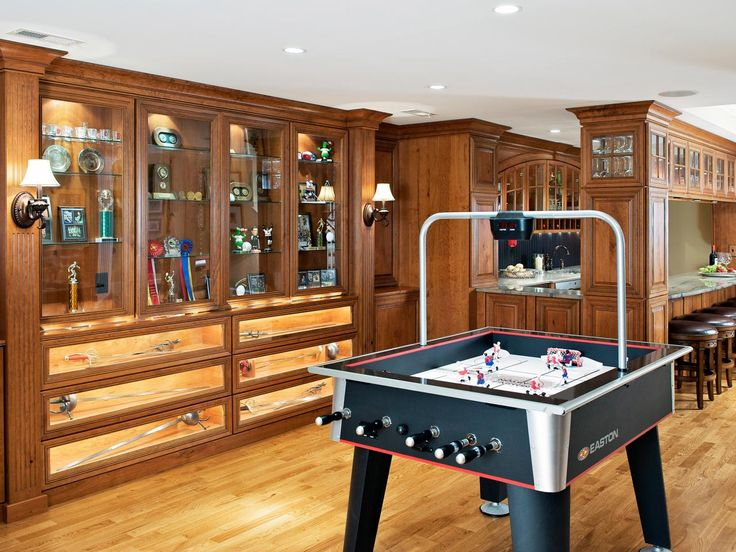 This traditional basement features built-in cabinetry to showcase sports memorabilia. Nearby, a wet bar is the perfect spot for entertaining guests and grabbing snacks while playing foosball and other games.