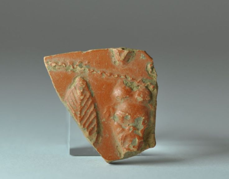 Teather mask on terra sigillata aretina, 1st century A.D. Teather mask on arretine ware shard with theater mask, 3.1 cm long. Private collection