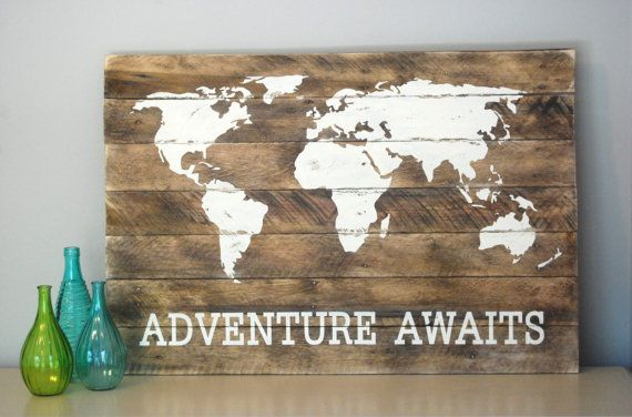 The world map and Adventure Awaits is painted on a reclaimed pallet wood sign. Both the map and lettering are white. Board is lightly stained
