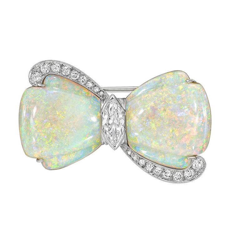 Carved opal and diamond bow pin, centering on a marquise-shaped diamond weighing approximately 0.71 carats (H-color/SI1 clarity) with eighteen full-cut and single-cut diamond accents weighing approximately 0.45 total carats, mounted in 18k and 14k white gold. 20th century.