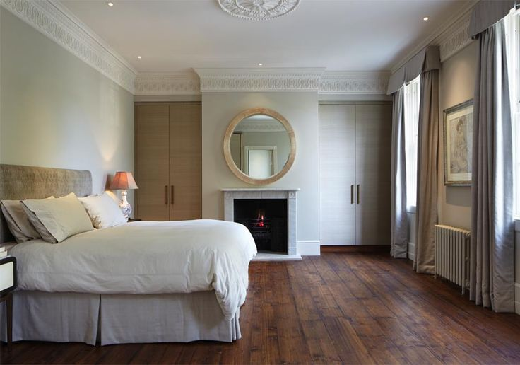 Tasteful Interior design for a listed period home in Richmond. The master bedroom contains original period fireplace and cornicing.