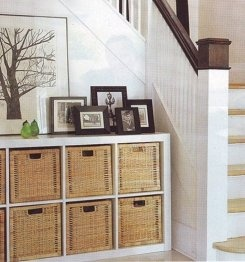 Expedit shelving with baskets in every section, to hold DVDs. In black-brown.