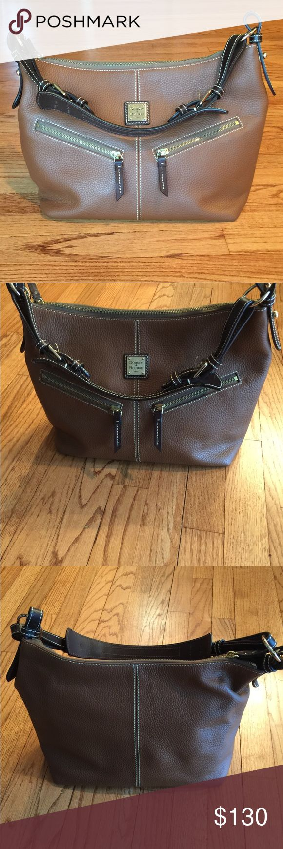 """BNWOT Dooney & Bourke BrownAllWeather Leather Hobo BNWOT Chocolate brown pebbled all weather leather. Excellent condition, never used. Comes with cosmetics case, key fob and dust bag.  Adjustable shoulder strap with buckle; zip-top close. Hobo bag interior: full lining, back wall zip pocket, front wall leather-trimmed cell phone pocket, leash for keys.   Hobo bag: measures 12""""W x 10""""H x 6-1/2""""D with an 8"""" to 10"""" strap drop; weighs 2 lbs, 3 oz Cosmetic bag: measures 6-1/2""""W x 4""""H x 2""""D  100%…"""