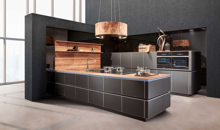 A kitchen with a rear-lacquered handleless glass front, here in matt black is accentuated with applications in 12mm cherry tree. The interplay of the matt black surfaces with the natural wood tones combines modern, classic design with pleasant homely accents.