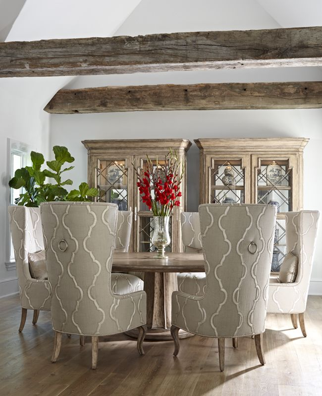 Dining Room. handle tall wing backs. round table. two hutches. white and beams.