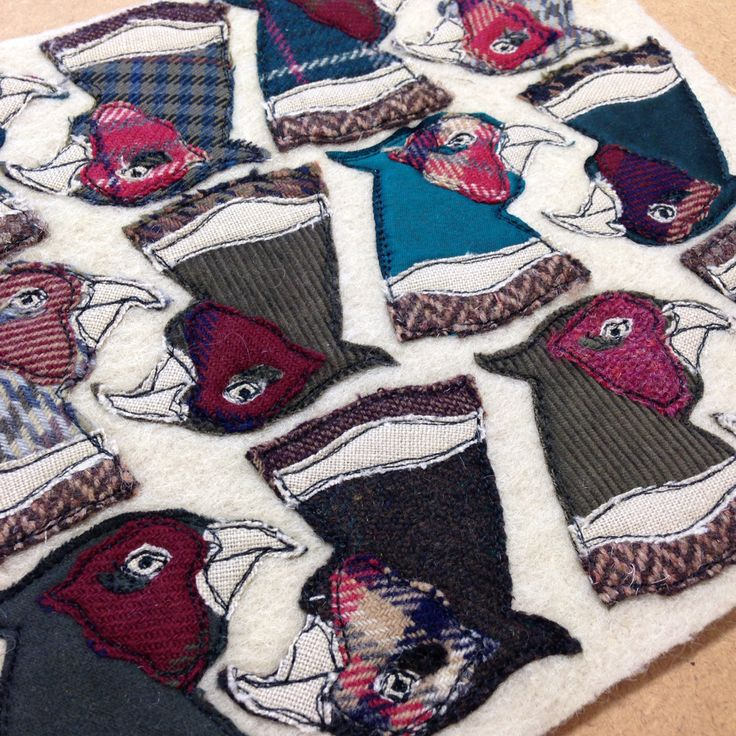 Appliqué and embroidered pheasant head brooches made from reclaimed materials.