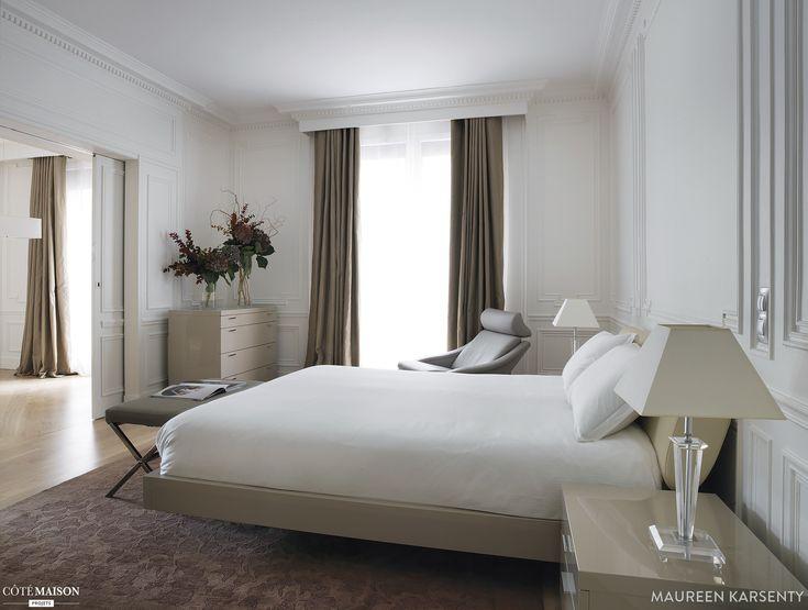 Une chambre à la déco classique. Grand lit blanc. Rideau marron. Grand tapis.