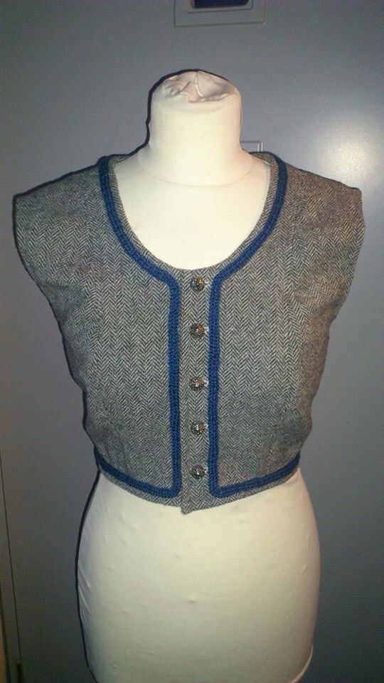A gray vest with a quick-knitted blue lining. The fabric is wool with a fishbone pattern. The buttons are silver and the entire vest is hand sown.