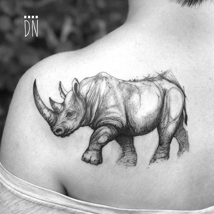 Sketchy rhino tattoo on the left shoulder blade.