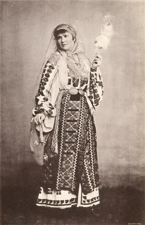 Queen Elizabeth of Romania in national costume with distaff and spindle.