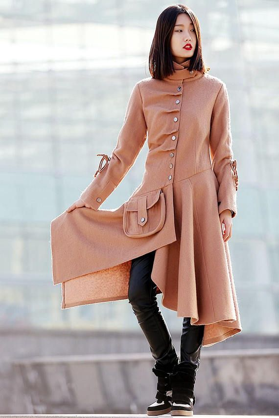 Whether for day or night, this asymmetrical swing coat is a chic essential for autumn/winter and one that will get you noticed. The cinched waist and large pocket detail will complement and flatter any woman and make you stand out in the crowd.  This is a statement jacket with the most exquisite details. Soft and warm, the trendy feminine shape grazes along the figure and creates a light sweep of fabric that gracefully moves with you as you walk. Details include a military style tab clos...