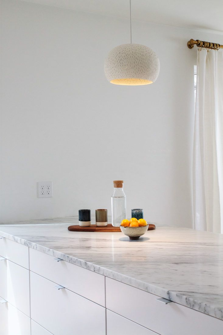 Ikea Veddinge cabinets topped with Arabescato Marble Countertops. Bright white kitchen rehab boston cabinet detail from Remodelista