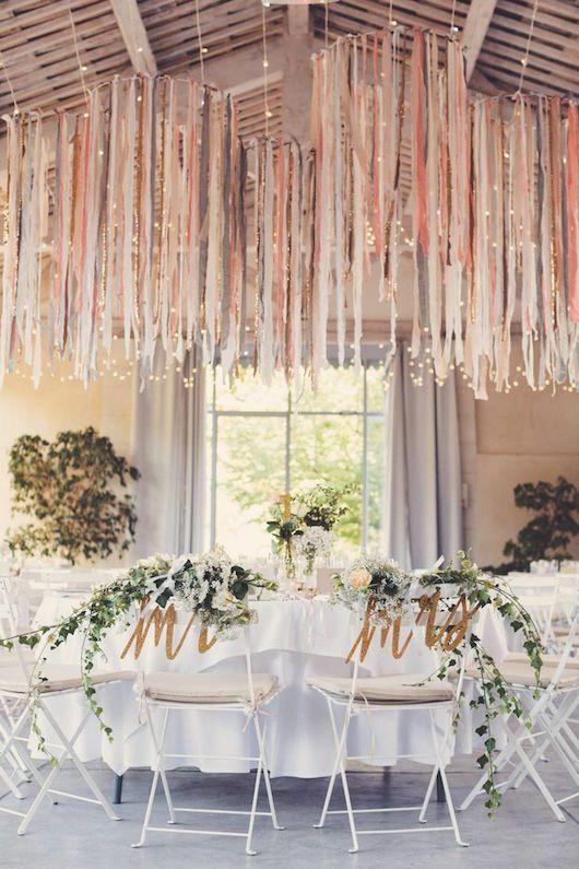 Centros de mesa colgantes con cintas en tonos complementarios a la boda…