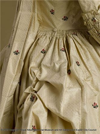 Detail of covered button and string used to gather the skirt back into a polonaise. Gown, 1775-1785, England, silk brocade- Royal Albert Memorial Museum & Art Gallery