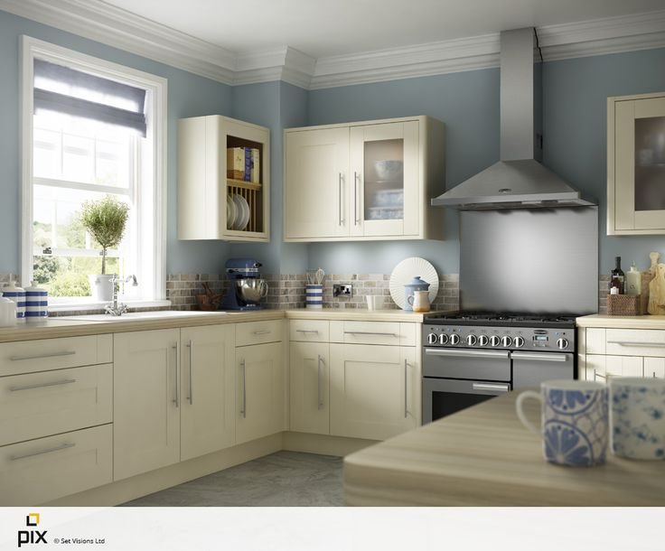 This soft cream painted shaker kitchen is great for any home renovation. The layout idea is practicle with island, range cooker, mixture of glazed and open wall units, with the large sash window adding character through architecture. Stainless steel splashback with rumbled travertine wall tiles. Photography by http://www.setvisionspix.co.uk/