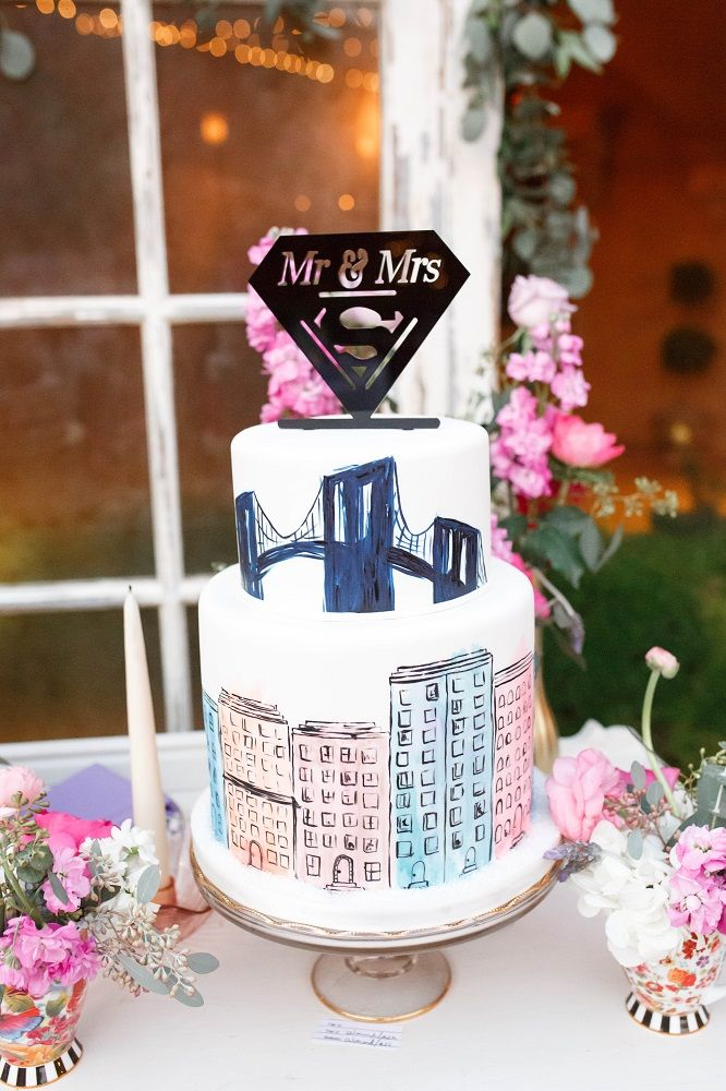 Colorful city buildings and bridges water pained on white fondant cake with black superman Mr. and Mrs. topper surrounded by pink and white flower | Monique Hessler Photography | villasiena.cc