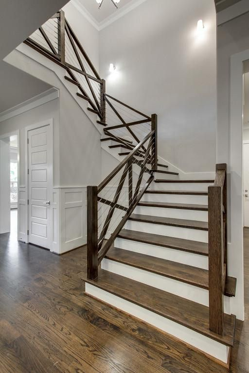 Make your stairs stand out! Cable wires and a dark wood stain offset pale gray walls in this farmhouse staircase