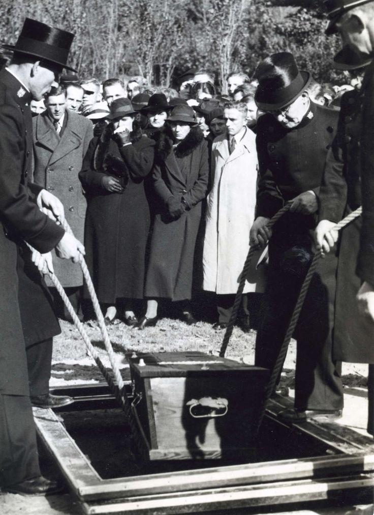Tweede Wereldoorlog : Begrafenis van slachtoffers van Engels bombardement op Haarlem. De kist wordt door twee grafdelvers / begrafenisondernemers het graf in gezakt, in het midden daarachter drie huilende vrouwen. Nederland, 1940.