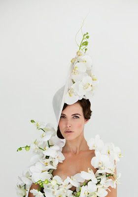 Philip Treacy - mad hatter ideas a creamy, pale green triangular hat inspires me to explore tall designs. the flowers are positioned inside the triangle shape and creates a neat 3D design.