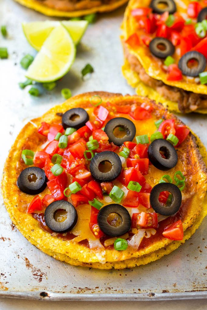 This Mexican pizza recipe is layers of taco meat and beans sandwiched between two crispy shells and topped with plenty of melted cheese and toppings.