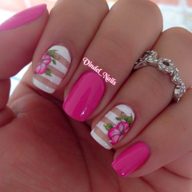 pink mani with striped accent nails and hibiscus stickers