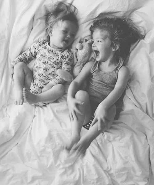 siblings laughing in bed
