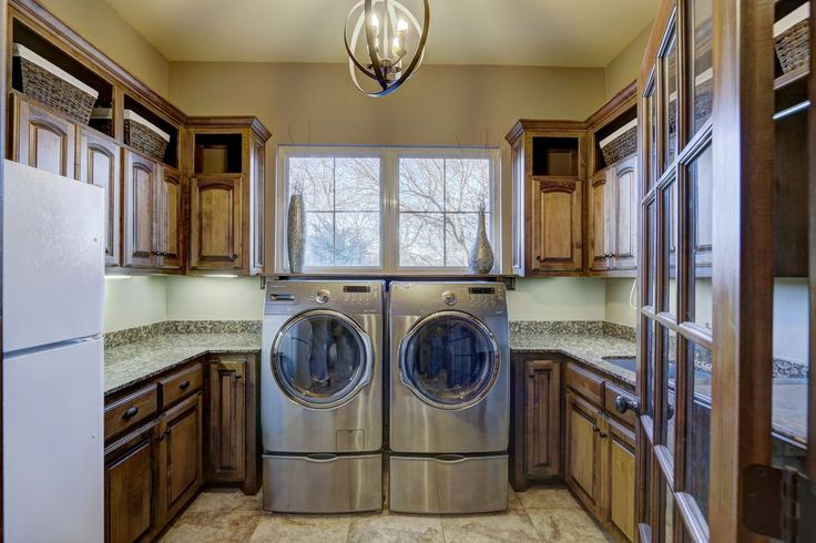 Laundry room with warm wood cabinetry and lots of storage.  #laundryroom homechanneltv.com