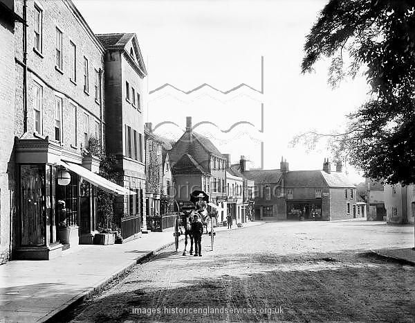 MARKET PLACE, Fairford, Gloucestershire. A woman in a horse and trap outside a clothier's shop in the picturesque cotswold town. Photographed in 1890 by Henry Taunt.