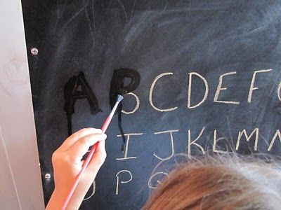 Tracing chalk letters with water to erase