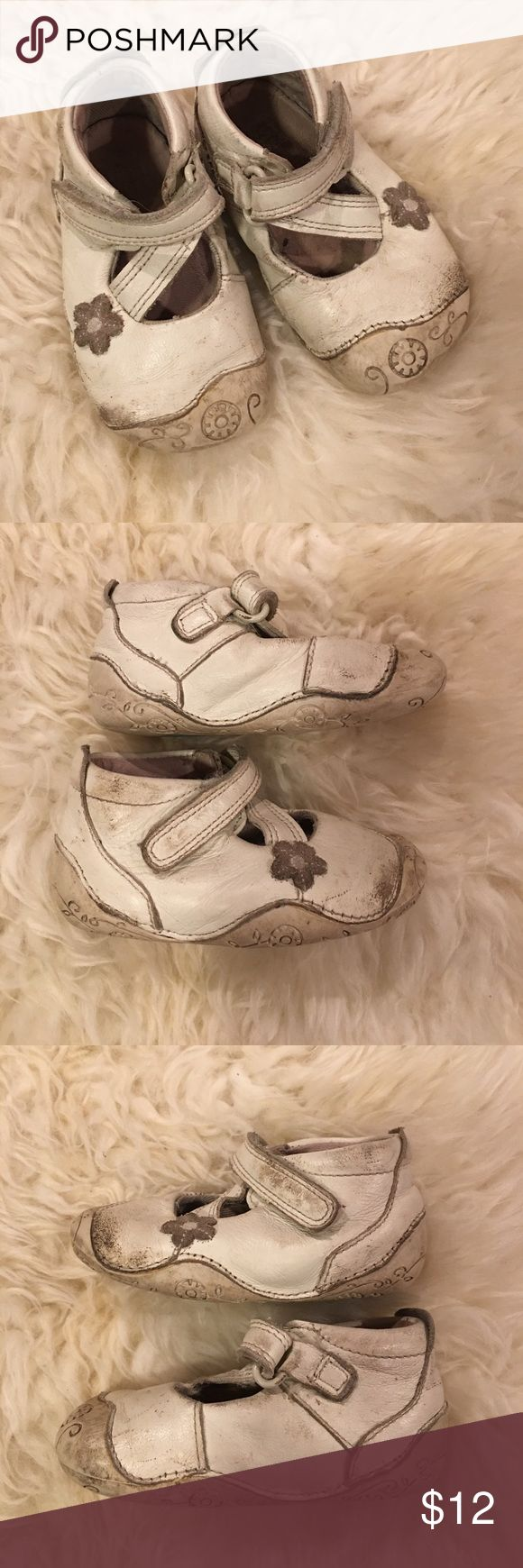 Clarks white leather baby girl shoes 3.5 Clarks first shoes in white leather with floral accents. Super flexible rubber sole and toe, perfect for crawlers and beginning walkers! These were my daughter's favorite pair. The leather has some wear and dirty parts. White shoe polish could probably make them look cleaned up, but structurally they're in great condition for more play! Size 3.5 m Clarks Shoes Baby & Walker