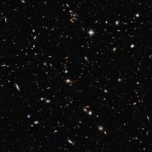 It's Galaxies all the Way Out!: This image shows a galaxy cluster set against a backdrop of more distant galaxies. This is a remarkable cross-section of the universe, showing objects at different distances and stages in cosmic history. They range from cosmic near neighbors to objects seen in the early years of the universe.