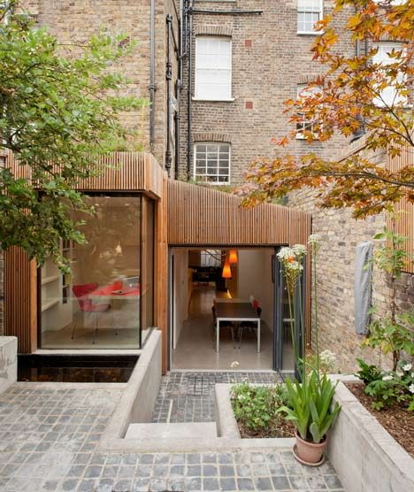 Adjoining the rear of the listed house, the timber-clad extension contains a study and a dining room with an oversized glass door to the garden.