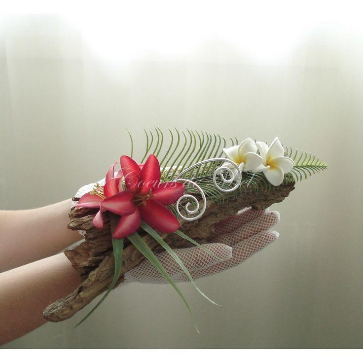 Boisé et coloré, ce porte alliance sera idéal pour un mariage au thème exotique. Réalisé à partir d'une écorce, ce coussin d'alliance est orné de fleurs de frangipanier et de fleurs de lys fuchsia. Vous pourrez y maintenir vos alliances grâce à deux arabesques argentées.
