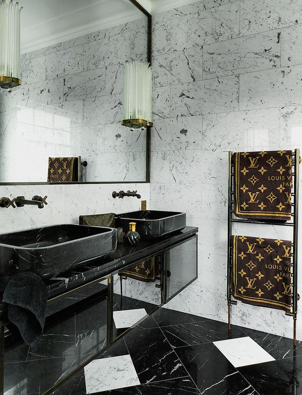 black marble consoles with mirrored finish, white marble tiled walls, deco scones, and louis vuitton towels.
