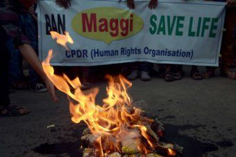 Indian activists burn packets of Nestle's Maggi instant noodles