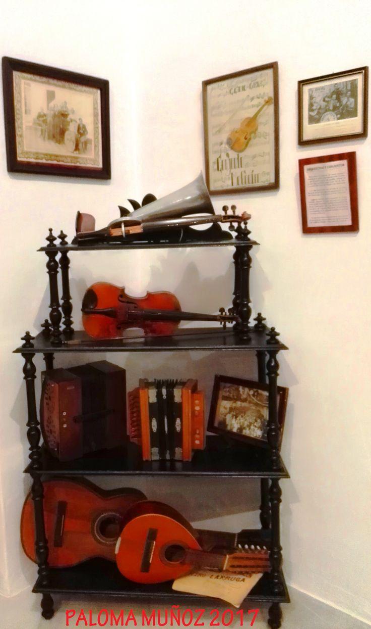 Un rincón de la Sala de música en el que se exponen instrumentos musicales como acordeones, violín, y varios tipos de guitarras. Music room. A corner of the music room in which musical instruments such as accordions, violin, and various types of guitars are on display.