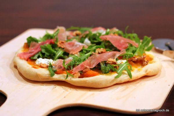 Kürbis-Pizza mit Rucola und Ziegenfrischkäse, dazu Walnüsse und Parmaschinken