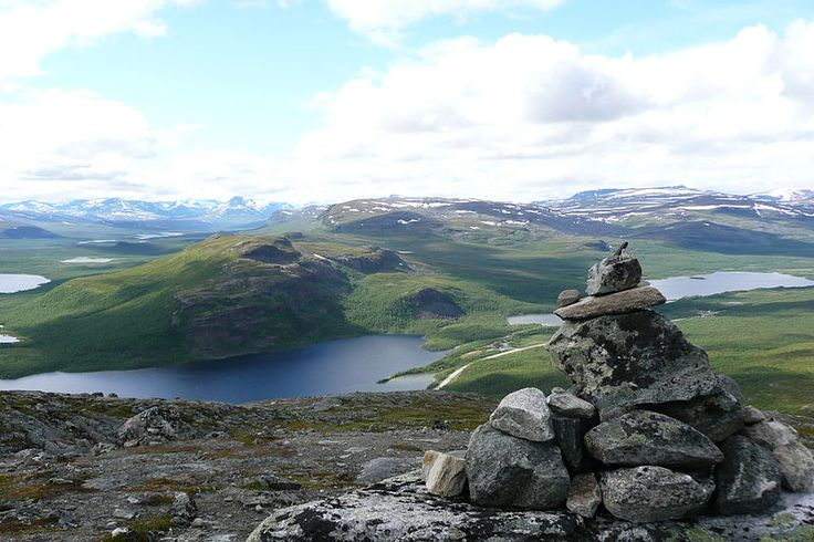 A view from Saana fell in the municipality of Enontekiö in Lapland, Finland. The stones on the right are one of the several stone stacks that the numerous visitors to Saana have gathered to the top of the fell. On the left a part of lake Kilpisjärvi is visible. The lake on the right is called Siilasjärvi. The closest fell in the picture is Pikku-Malla and behind that is Iso-Malla, both in the Malla Strict Nature Reserve.